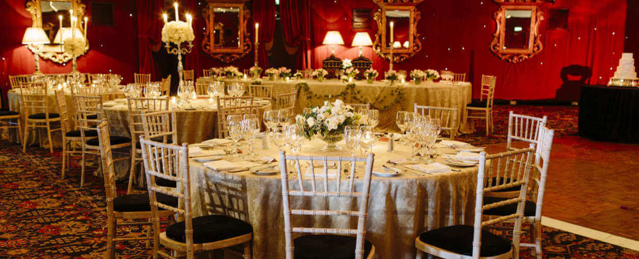 An ornate room layed up for an event with flowers and candles at a luxury hotel in Edinburgh.