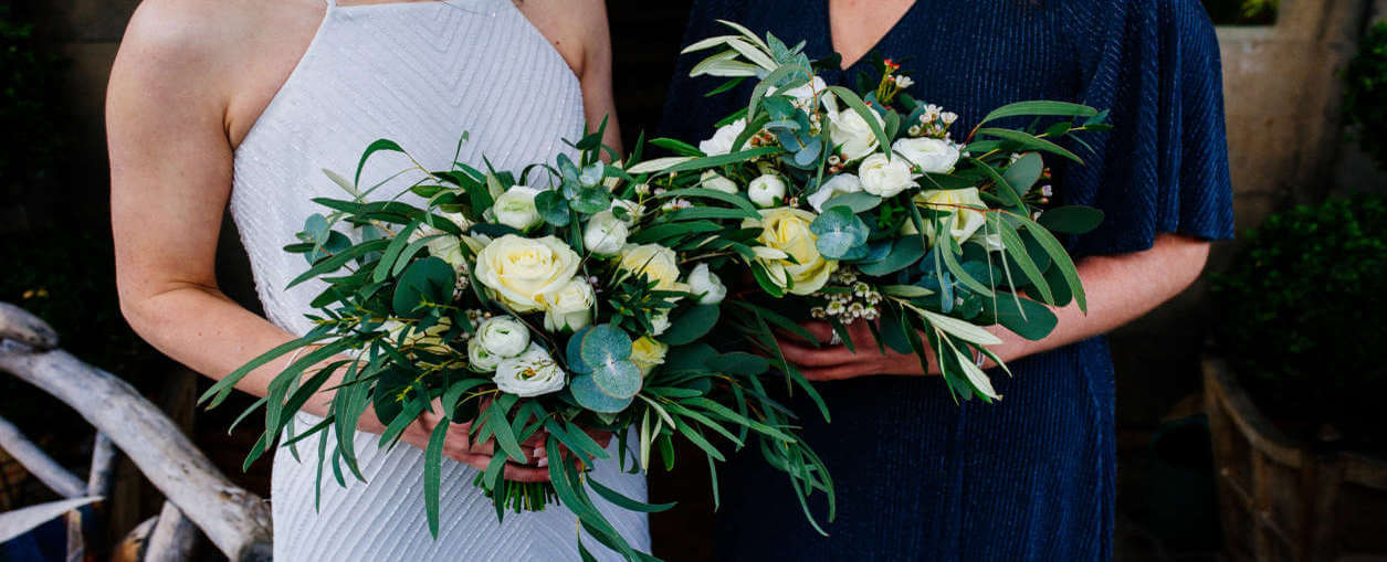 Two women carrying bouquets of white flowers at a wedding in Edinburgh, at Prestonfield House.